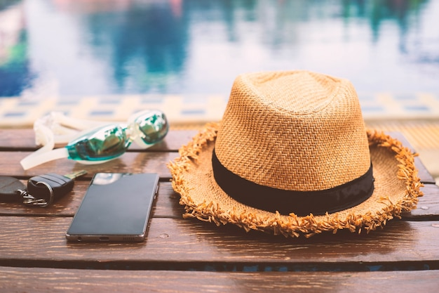 The hat is placed at the wooden table side the swimming pool with smartphone and goggle.vintage style Premium Photo