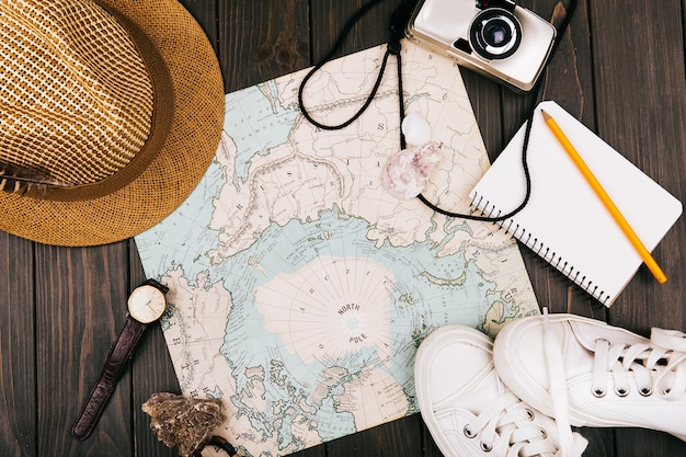 Hat, map, notebook, camera, watch and keds lie on a travel map Free Photo