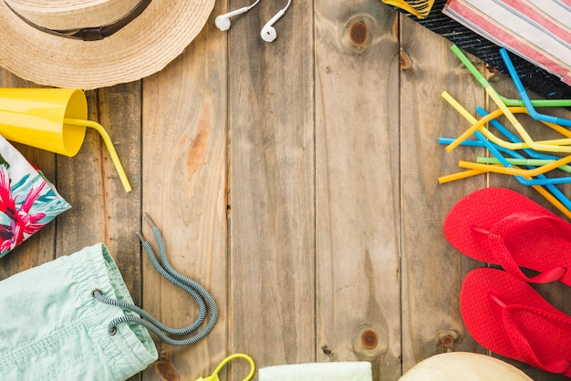 Hat near earphones and flip flops with cup and straws Free Photo