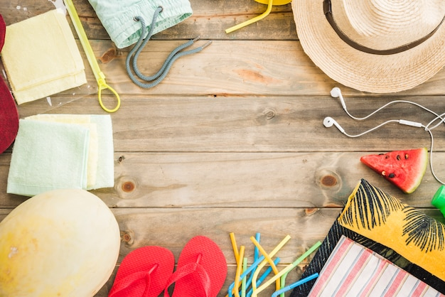 Hat near earphones and flip flops with fruits and vacuum bag Free Photo