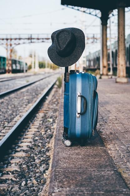 모자는 기차역에서 가방에 자리 잡고 있습니다. 프리미엄 사진