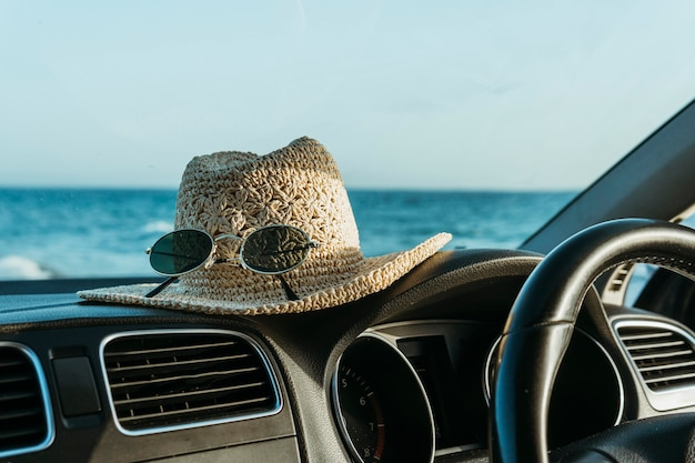 Hat and sunglasses on car board Free Photo
