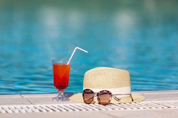 Hat sunglasses and drink near pool Free Photo