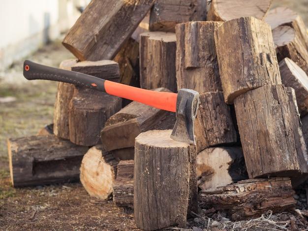 伐採された木の背景に木を収穫するための手hatch。 Premium写真