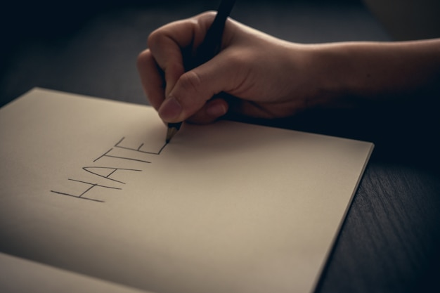 Hate concept - hand writing hate on book Free Photo