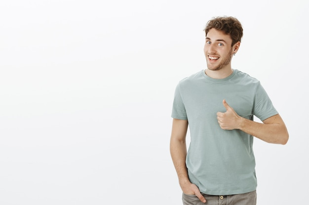 Have not heard ideas better. portrait of positive good-looking male model with bristle in earrings, turning head in profile and smiling broadly while showing thumbs up Free Photo