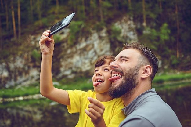 Веселиться. отец пример благородного человека. принимая селфи с сыном. ребенок катается на плечах папы. счастье быть отцом мальчика. Premium Фотографии