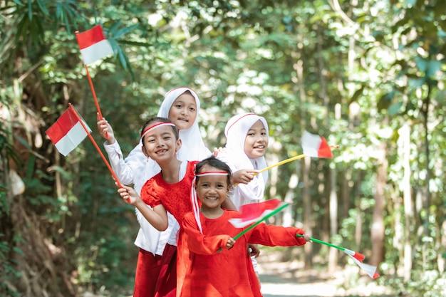 Веселая группа азиатских маленьких девочек держит красно-белый флаг и вместе подняла флаг Premium Фотографии