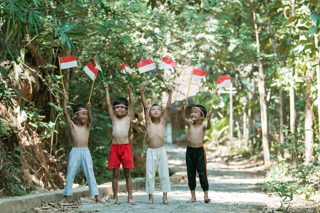 Веселая группа детей, стоящих без одежды, держа маленький красно-белый флаг Premium Фотографии