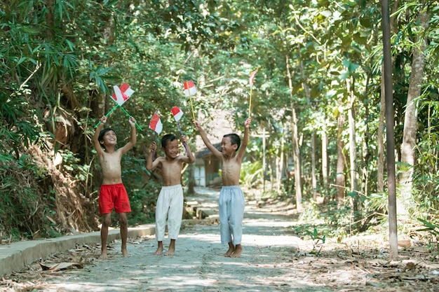С удовольствием трое мальчиков, стоящих без одежды с маленьким красно-белым флагом Premium Фотографии