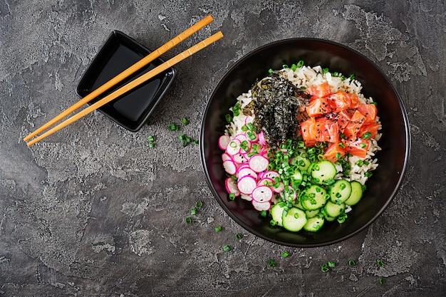 Hawaiian salmon fish poke bowl with rice, radish,cucumber, tomato, sesame seeds and seaweeds. buddha bowl. diet food. top view. flat lay Free Photo