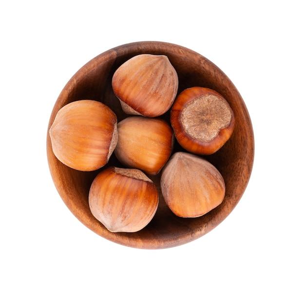 Фундук в деревянной миске, изолированной на белом. макрос ореха. с обтравочным контуром. вид сверху. Premium Фотографии