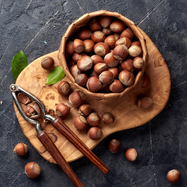 Hazelnut with nutcracker on olive wooden board. nut with green leaves. Premium Photo