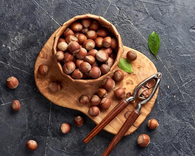 オリーブの木の板にくるみ割り人形とヘーゼルナッツ。緑の葉とナッツ。上面図。 Premium写真