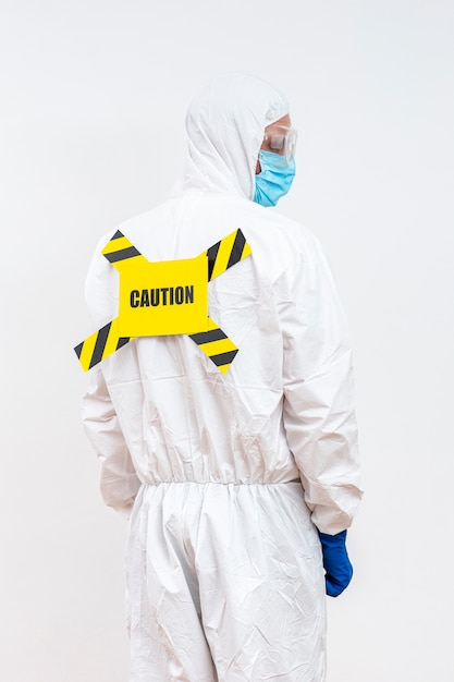 Человек в костюме hazmat со знаком опасности Бесплатные Фотографии