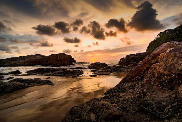 Hdr自然の岩とタイ南島の海のビーチ上の劇的な日没。 Premium写真