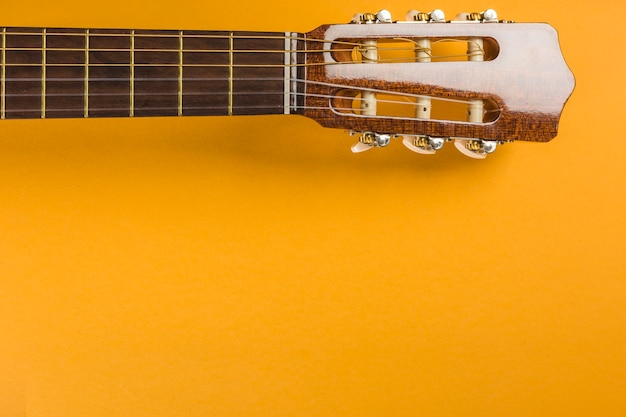 Head of classical acoustic guitar on yellow background Free Photo