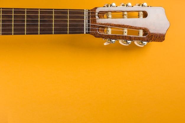 黄色の背景に古典的なアコースティックギターのヘッド Premium写真