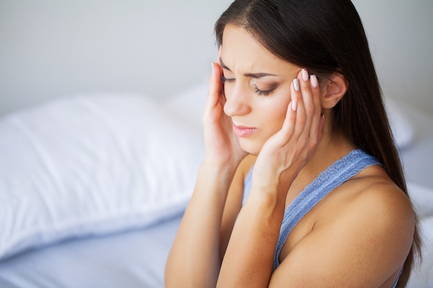 Head pain. attractive young woman wake up on her bed looking unhappy and feeling sick. Premium Photo