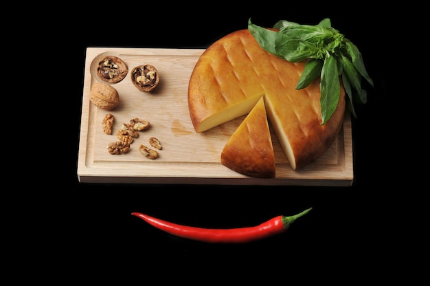 Head of smoked suluguni cheese on wooden board with walnuts and basil on black surface Premium Photo