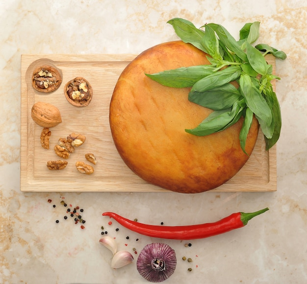 Head of smoked suluguni cheese on wooden board with walnuts and basil on the marble surface Premium Photo