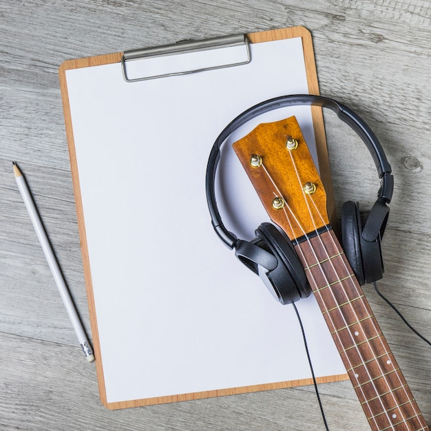 Headphone over the guitar headstock over the white paper on clipboard with pencil Free Photo