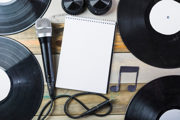 Headphone; microphone; vinyl record and blank spiral notepad with musical note on wooden table Free Photo