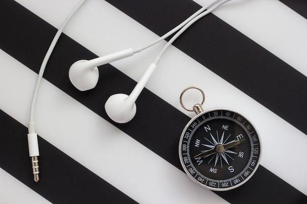 Наушники и компас на черно-белом фоне, крупным планом Premium Фотографии