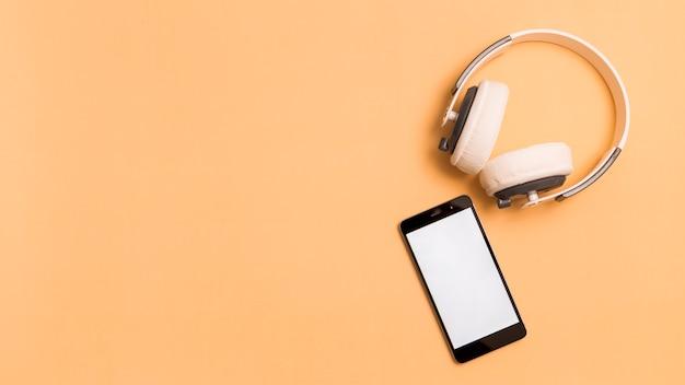 ヘッドフォンとオレンジ色の背景上のスマートフォン Premium写真