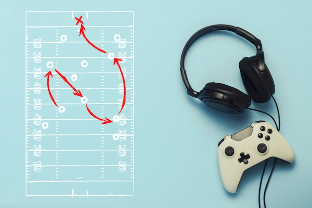 Headphones and gamepad on a blue background. added drawing with the tactics of the game. american football. the concept of computer games, entertainment, gaming, leisure. flat lay, top view. Premium Photo
