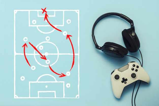 Headphones and gamepad on a blue background. added drawing with the tactics of the game. football. the concept of computer games, entertainment, gaming, leisure. flat lay, top view. Premium Photo