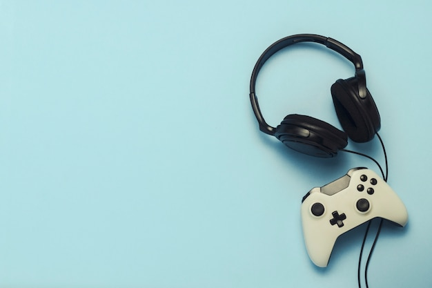 Headphones and gamepad on a blue background. . concept of computer games, entertainment, gaming, leisure. flat lay, top view Premium Photo