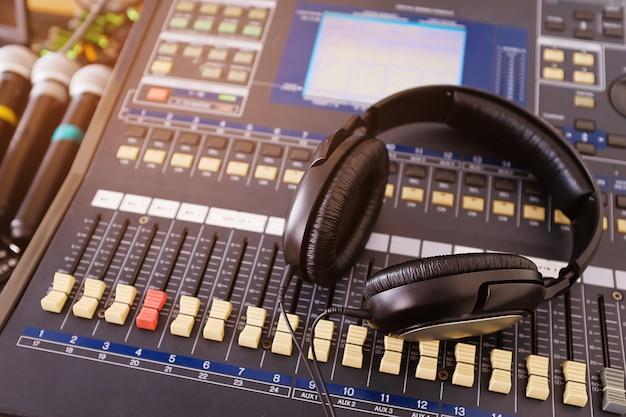 Headphones, microphones and amplifying equipment on studio audio mixer knobs and faders. Premium Photo