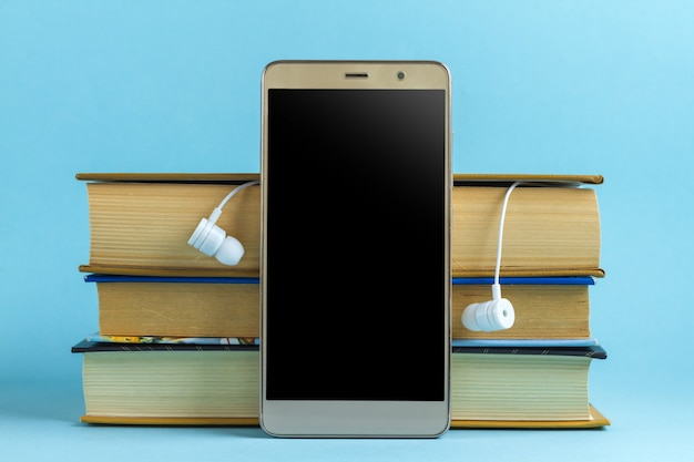 Headphones, mobile phone and books. audio book concept. reading books without looking up from work Premium Photo