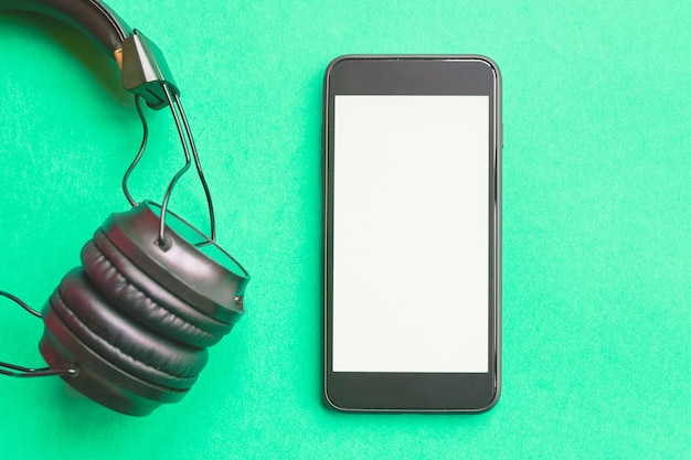 Headphones and smartphone on colorful background. Premium Photo
