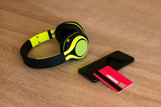 Headphones, smartphone and credit card on a table Premium Photo