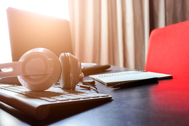 Headphones, tablet computer and laptop on black table Premium Photo