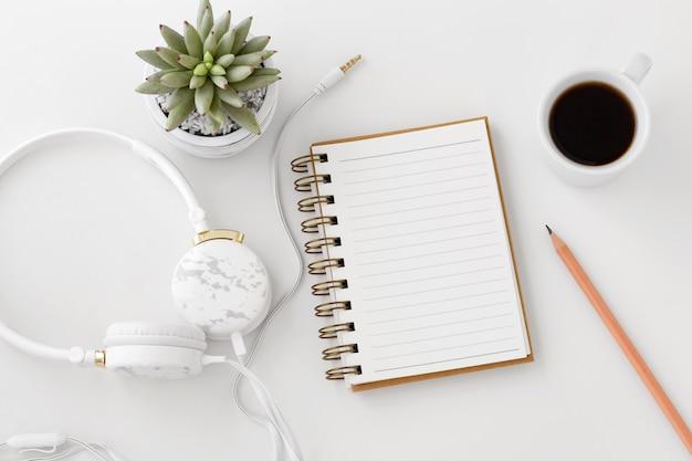 Headphones with notebook on white desk Premium Photo