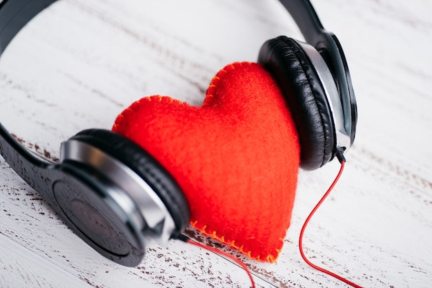 Headphones with red heart on table Free Photo