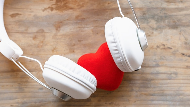 Headphones with red heart on wooden table Free Photo