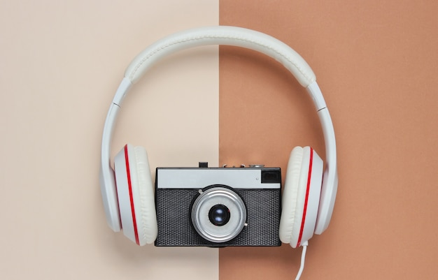 Headphones with a retro camera on a brown-beige background. top view, minimalism Premium Photo