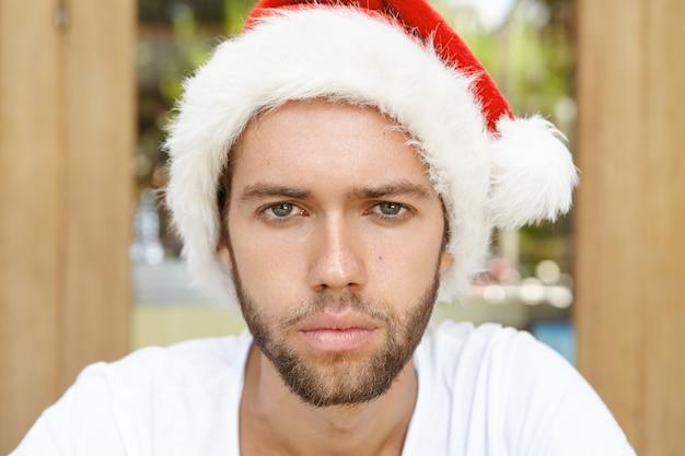 Primo piano del volto di attraente giovane uomo con la barba lunga che indossa il cappello di babbo natale che sembra infelice Foto Gratuite