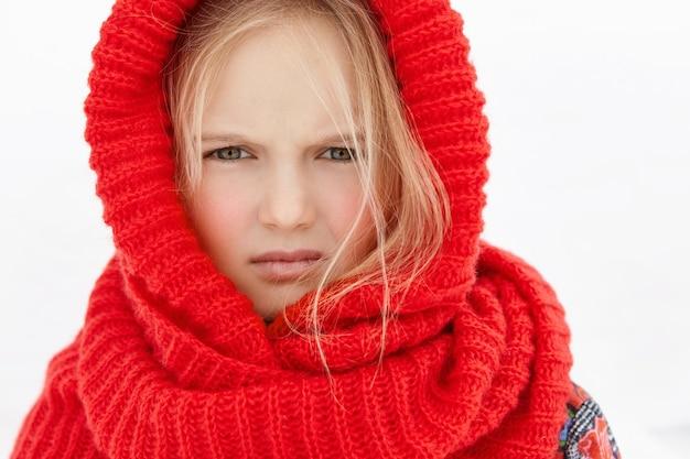 Headshot di bella bambina caucasica bionda che porta sciarpa di lana rossa intorno alla testa ed al collo Foto Gratuite