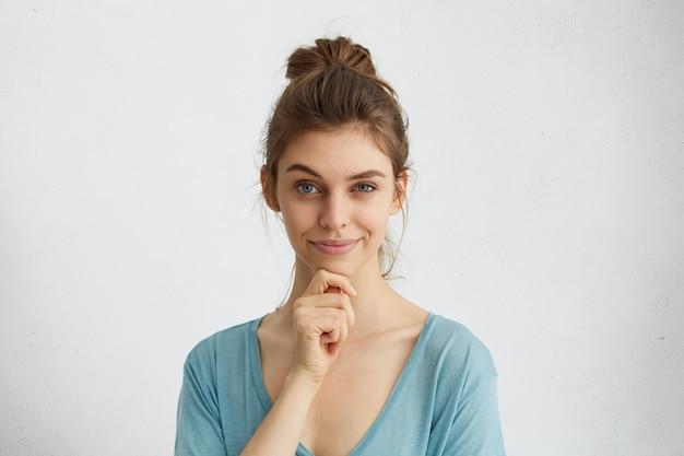 Primo piano del volto di bella donna con uno sguardo astuto alzando il sopracciglio e tenendo la mano sul mento avendo alcuni piani complicati nella sua mente. Foto Gratuite