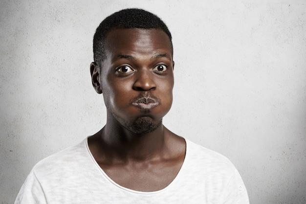Primo piano del volto di un giovane africano con gli occhi da insetto che fa smorfie, gonfiando le guance, trattenendo il respiro, sforzandosi di non ridere con l'espressione del viso buffo, facendo clown e divertendosi al chiuso Foto Gratuite