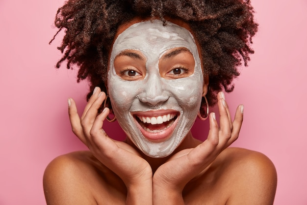 Headshot of cheerful girl with white clay mask, touches face, takes care of skin and beauty, has positive smile, afro haircut, models over pink wall, poses indoor. facial treatment concept Free Photo