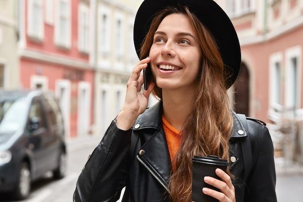 Il colpo alla testa del passeggero femminile fa una conversazione telefonica, guarda felicemente da qualche parte, si erge contro lo spazio urbano sfocato Foto Gratuite