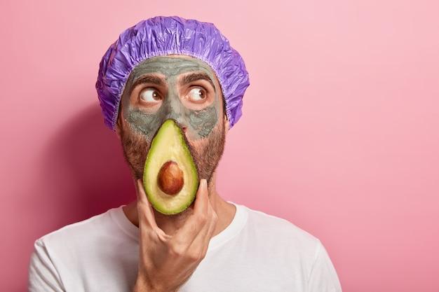 Il colpo alla testa dell'uomo concentrato guarda in alto, tiene una fetta di avocado vicino al viso, applica la maschera all'argilla, rimuove i punti neri sulla pelle Foto Gratuite