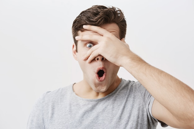 Headshot of goofy surprised bug-eyed young european male student wearing casual grey t-shirt staring  with shocked look, expressing astonishment and shock, hiding face behind his palm. Free Photo