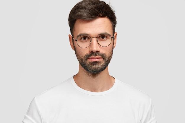 Primo piano del volto di un bel freelance maschio con un aspetto accattivante, ha barba e baffi scuri, guarda direttamente con uno sguardo serio, indossa abiti casual bianchi. monocromo. espressioni facciali. Foto Gratuite